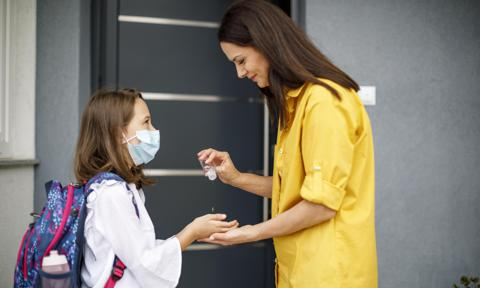 Mother sanitizing her daughter's hands with antibacterial hand spray before going to school
