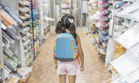 Rear View Of Girl With Backpack Standing In Store