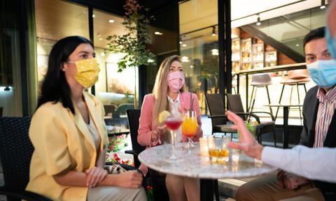 Small group of young people with protective face masks sitting in an outdoor bar terrace at night, talking, relaxing, and drinking