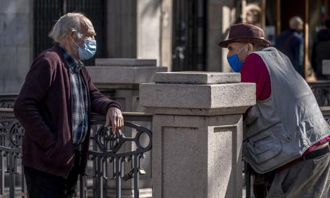 Two retired men wearing face masks talking to each other in