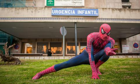 A man dressed as Spiderman poses outside the hospital during